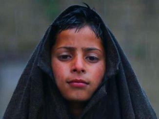 A Kashmiri boy walking amidst rains while covering his head with his Pheran (Kashmiri gown)